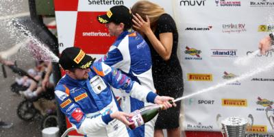 British GT Drivers open a bottle of champagne on the podium